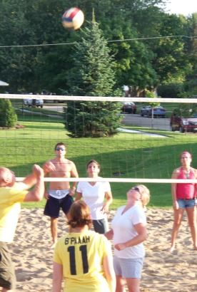 People Playing in a Volleyball Game in the Sand